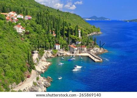 Adriatic sea shore with distant leisure white boats inside sunny harbor, Trsteno, Croatia - stock photo