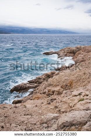 adriatic seashore with rocky coast and little raged sea, island krk, croatia - stock photo