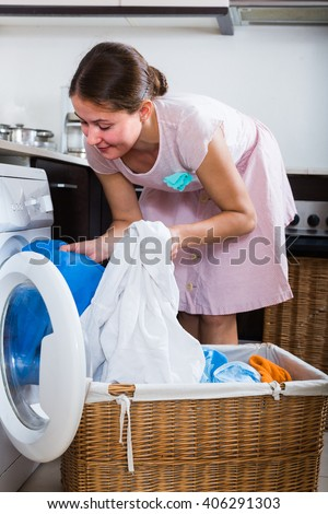 adult American housewife with basket of linen near washing machine indoors
