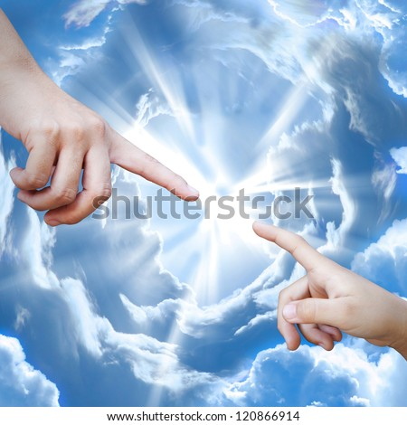 Adult and child hand against each other on the sky - stock photo