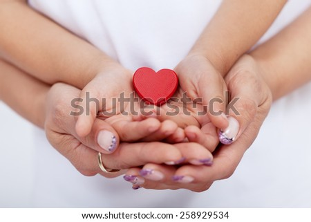 Adult and child hands holding red heart together-shallow depth of field - stock photo