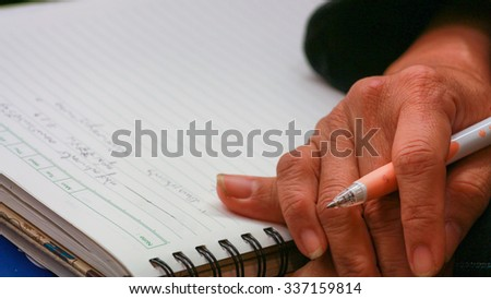 Adult Asian female lay hands on book - stock photo