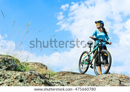 Adult attractive female cyclist  standing on a rock with her mountain bike.