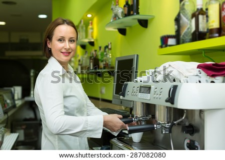 Adult barista girl making cup of coffee in cafe