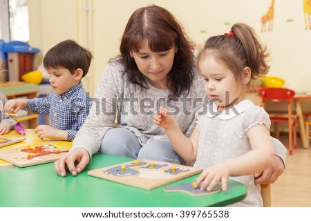 adult beautiful caucasian female teacher collect puzzle with a girl at the green table in the classroom. Horizontal color image