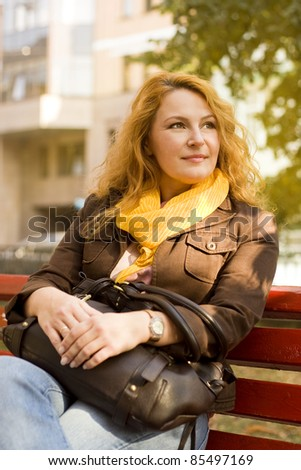 adult beautiful woman sitting on bench resting after work - stock photo