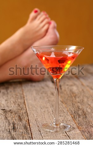 Adult beverage Cosmo colorful drink in martini glass on weathered, rustic tabletop with woman's feet - stock photo