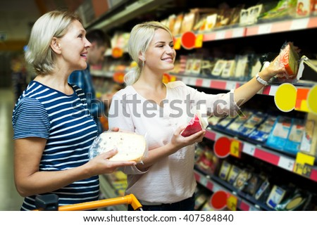 Adult blonde helping female pensioner to choose cheese in shop - stock photo