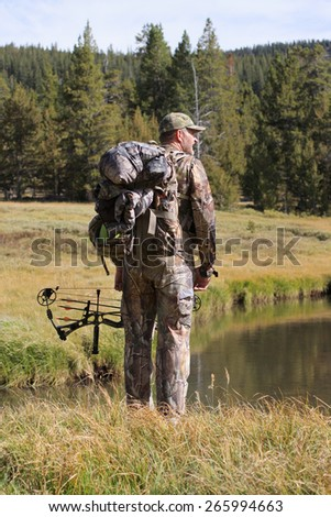 adult bowhunter by stream in remote forest