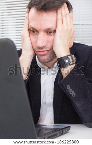 adult business man looking at screen laptop computer with a shocked upset expression, tired because of work - stock photo