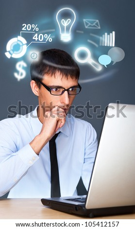 Adult business man working with his computer and different icons of his tasks and functions are flying from screen