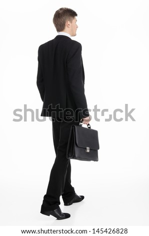 Adult businessman carrying a briefcase walking away - stock photo