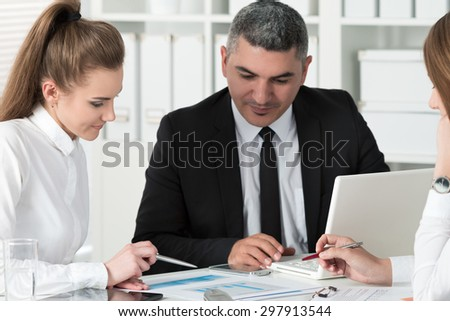 Adult businessman consulting his young female colleague during business meeting. Partners discussing documents and ideas - stock photo