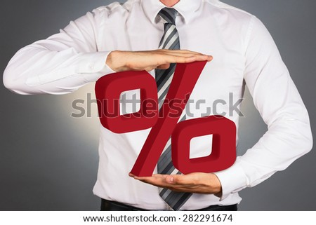 Adult businessman holding 3 D percent sign, isolated on dark background.  - stock photo