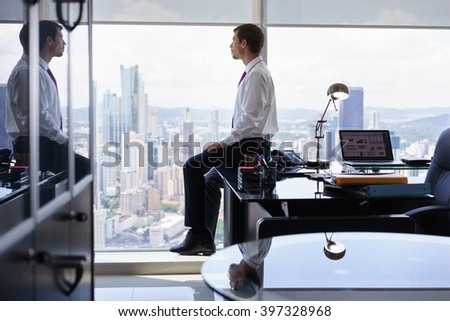 Adult businessman sitting on desk in modern office and looking out of the window, with pensive expression. The man contemplates the city and skyscrapers. - stock photo