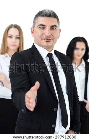 Adult businessman standing in front of his colleagues offering his arm for handshake. Group of business people isolated on white background. - stock photo