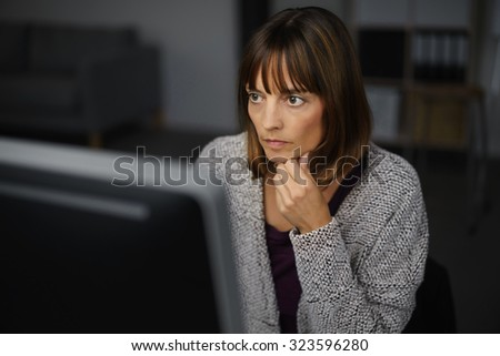 Adult Businesswoman Working on her Computer Seriously Beyond Office Hours. - stock photo