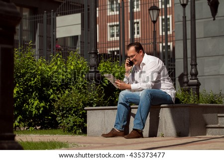 Adult caucasian businessman with computer sitting outdoors sunny day