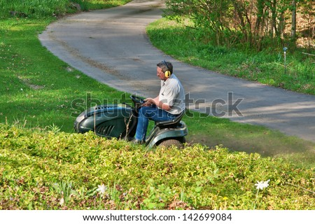 adult caucasian man on a lawnmower mowing grass lawn in late spring afternoon - stock photo