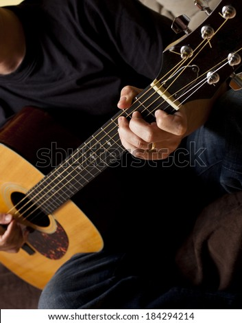 Adult caucasian man playing acoustic guitar