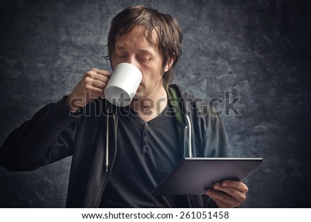 Adult Caucasian Man Reading News on Digital Tablet Computer Device and Drinking Coffee - stock photo