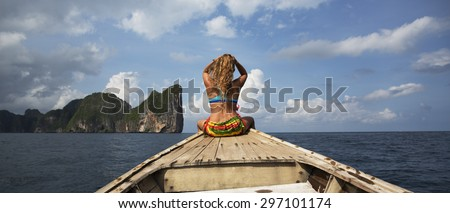 Adult Caucasian woman in blue swimsuit with back turned to camera is sitting on a boat and stroking down her hair against vibrant cloudy seascape. - stock photo