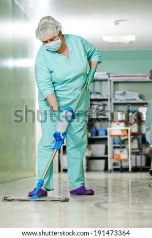 Adult cleaner maid woman with mop and uniform cleaning corridor pass floor of pharmacy industry factory or medical clinic - stock photo