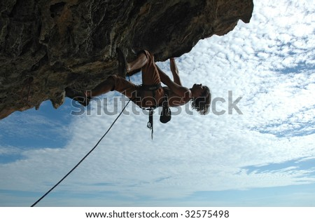 Adult climbing hard overhanging wall in Krabi, Thailand. Silhouette.