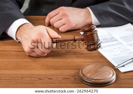 Adult. Close-up Of Male Judge Hand Striking The Gavel In A Courtroom - stock photo