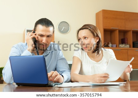 Adult couple calling by mobile about financial documents