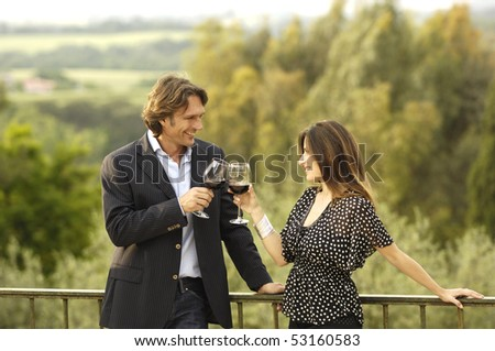 Adult couple celebrating with red wine - stock photo