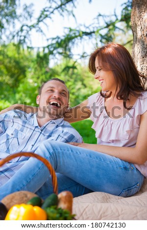 Adult couple picnicking in the summer park under the tree