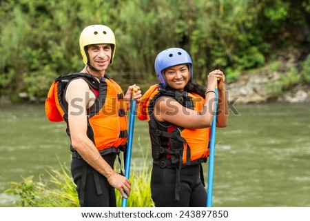 ADULT COUPLE PREPARED FOR WHITE WATER RAFTING TRIP, SPECIFIC EQUIPMENT  - stock photo