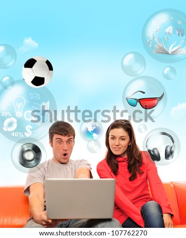 Adult couple sitting on sofa and having fun using their laptop. Different objects flying around them - stock photo