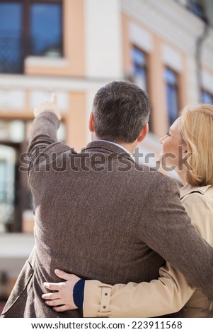adult couple standing outside and looking at house. man pointing to house window and hugging woman - stock photo