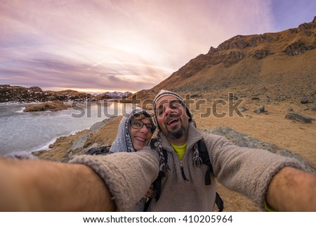 Adult couple taking selfie at sunset while hiking in the beautiful natural background of the italian Alps. Concept of freedom and adventures on the mountain. Wide angle fisheye lens. - stock photo