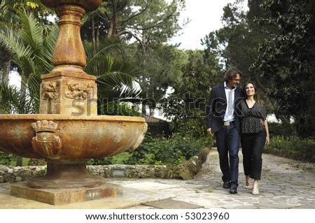 Adult couple walking in a villa - stock photo