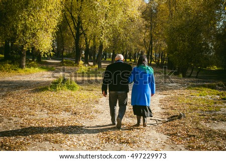 adult couple walking in autumn park. husband and wife walking outdoors in autumn last days