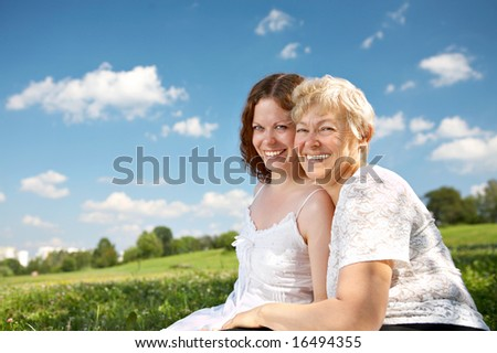 Adult daughter and her mother sit on a lawn and laugh