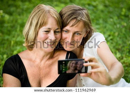Adult daughter and her senior mother are taking picture with mobile phone
