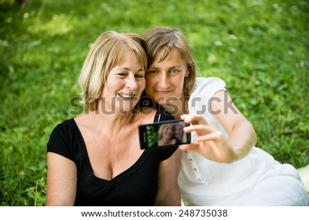 Adult daughter and her senior mother are taking picture with mobile phone - stock photo