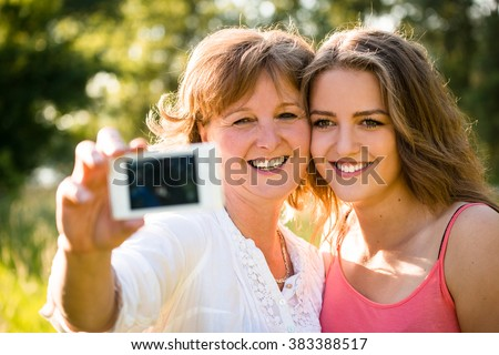 Adult daughter and her senior mother are taking selfie photo with mobile phone
