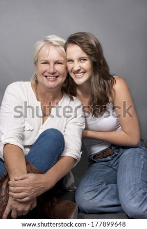 Adult Daughter and mom sitting hugging close - stock photo