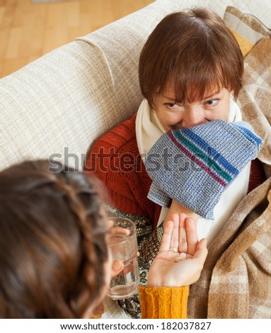 Adult daughter caring for sick mature mother has cough in living room
