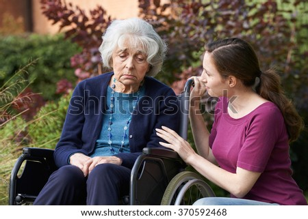 Adult Daughter Comforting Senior Mother In Wheelchair - stock photo