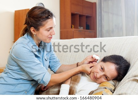 Adult daughter dripping eardrops to mature mother  in home