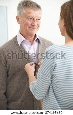 Adult Daughter Helping Senior Man To Button Cardigan - stock photo
