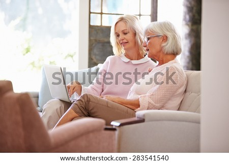 Adult Daughter Helping Senior Mother With Computer At Home - stock photo