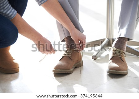 Adult Daughter Helping Senior Tie Shoelaces - stock photo