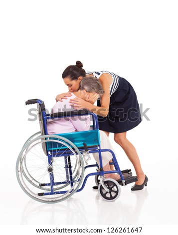 adult daughter hugging and comforting crying disabled senior mother